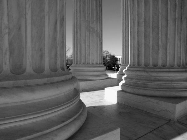 Black and white image of marble columns of supreme court.