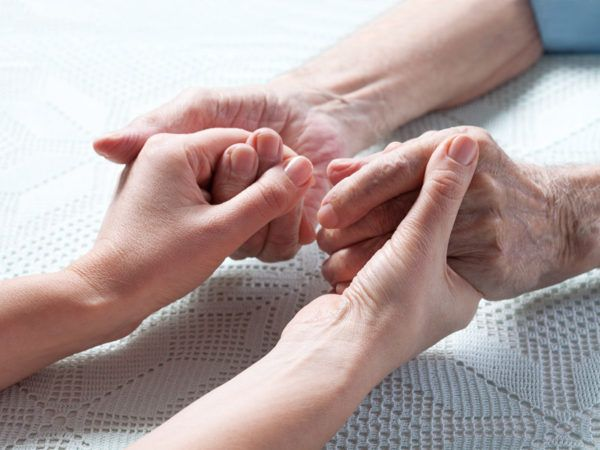 Two sets of hands holding each other. Young and elderly care concept.