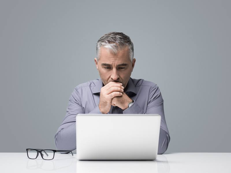 Middle aged man contemplating online purchase.