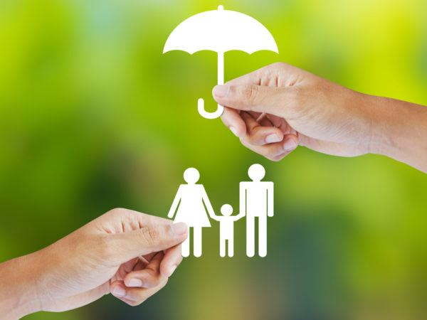 Hands holding paper cut-outs of family and umbrella. Life insurance concept.