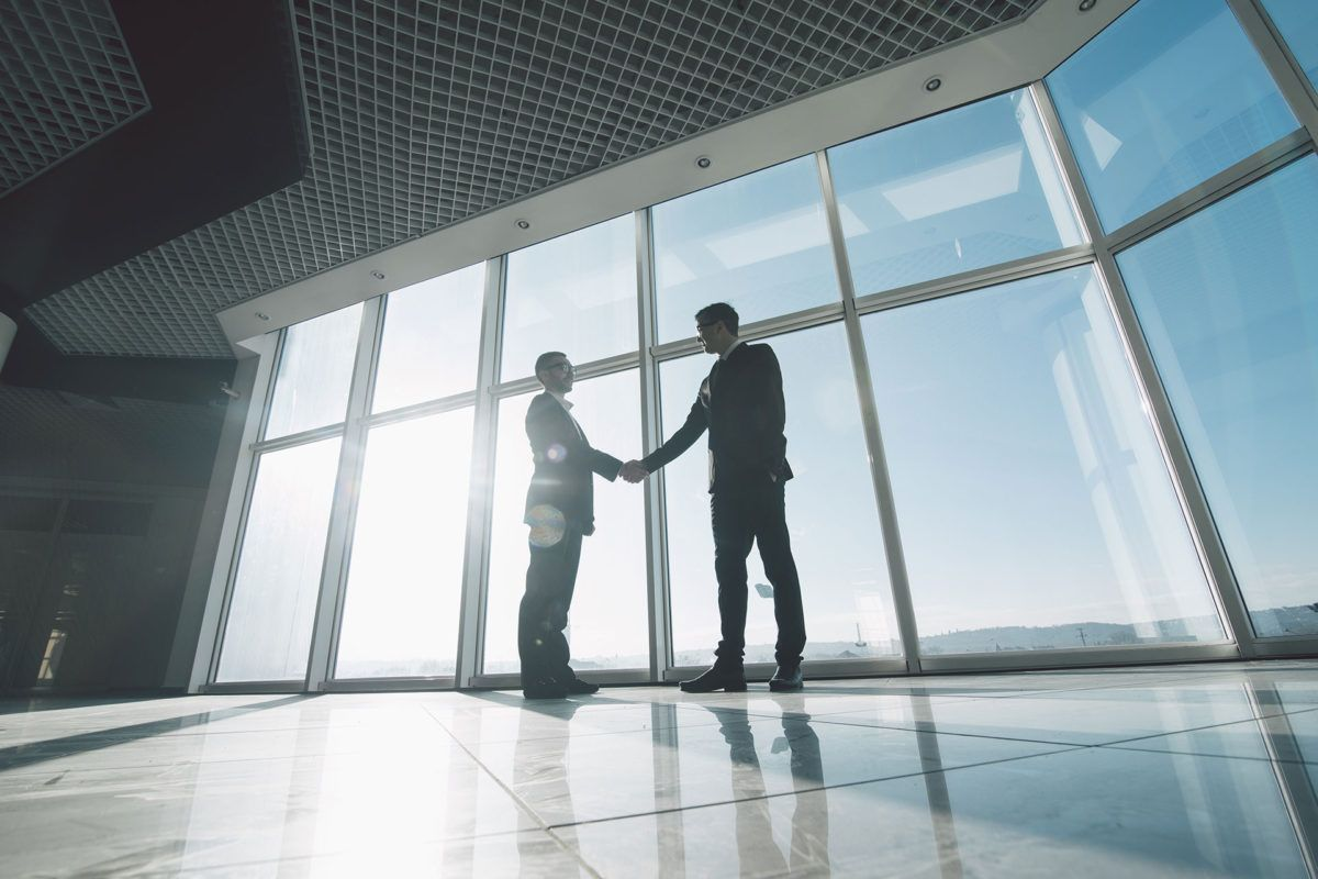 Two lawyers shaking hands in agreement in front of large windows.